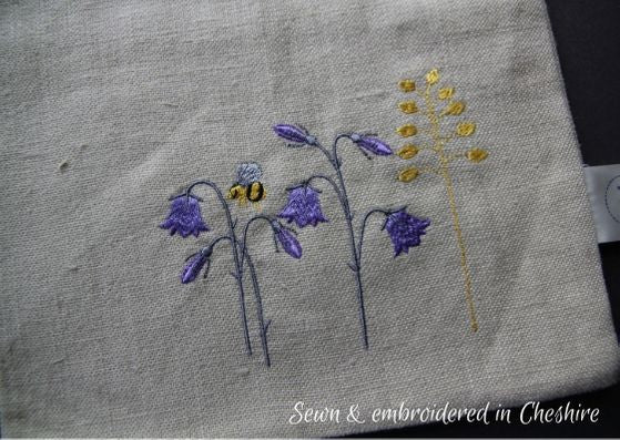 Close up of natural linen bag, embroidered with purple harebells, a yellow sprig of grass and a bumple bee.