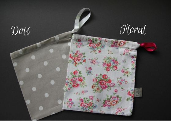 Two project bags lying on top of each other.  They are size small, beige colour with white dots on the left and a cream colour with a pink and green floral pattern on the right.