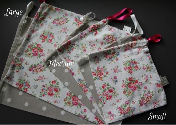 Six project bags lying on top of each other in a fan.  They range from large to medium, to small from left to right and alternate from a beige colour with white dots and a cream colour with a pink and green floral pattern.