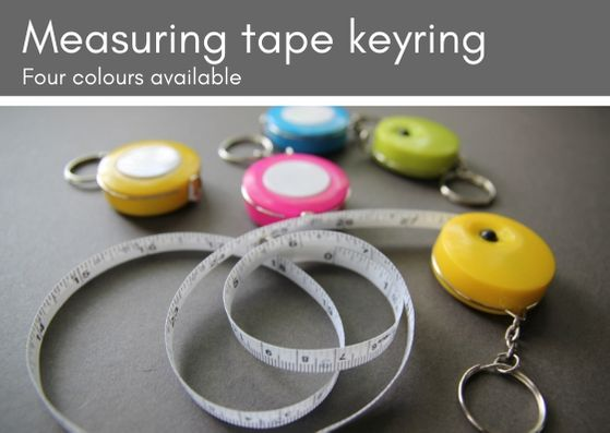 Grey background with five round measuring tape keyrings (two yellow, 1 each of pink, blue and green).  The second yellow one is at the front of the photo with the white tape unfurled.  Black buttons on top for retracting the tape and a silver keychain to attach.