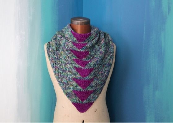 Arria crocheted shawl: The shawl is being worn by a mannequin against a background of blues and teals, painted in a rough vertical fade.