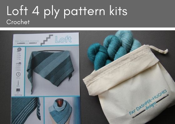 "Crochet kit for Loft shawl: on left is a hardcopy of the pattern showing the shawl off in three shades of teal and on the right are the three shades getting darker from right to left, all sat in a rolled back bag with ""Fay Dashper-Hughes Designs"" embroidered on it."