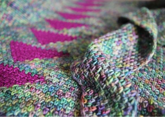 Arria crocheted shawl: close up f the shawl showing the spine of traingles in the bright pink against the variegated main colour - all crocheted in linen stitch.