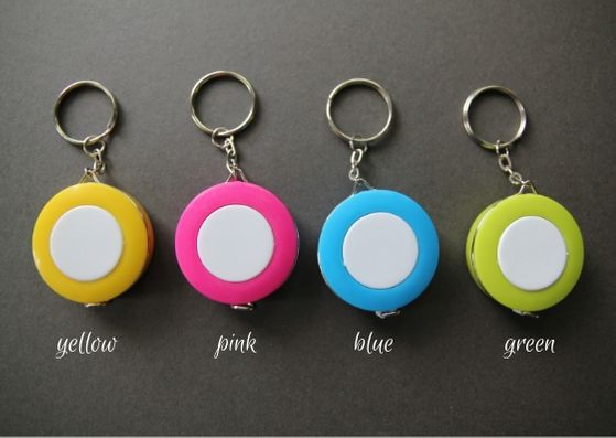Grey background with a line up of round measuring tape keyrings. L-R they are yellowm pink, blue and green and each has a white disc in the centre.