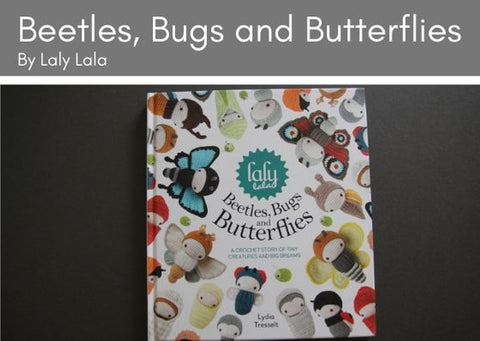 Beetles, Bugs and Butterflies by Laly Lala lies on a grey background.  The front cover is white with crcoheted bugs, beetles and butterflies all over it.