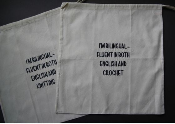 "Close up of two natural cotton bags with black text saying "" I'm bilingual - fluent in both English and crochet/knit""."