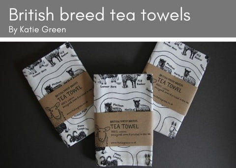 Three Katie Green folded white cotton tea towels printed with black and showing all 72 British sheep breeds.  Each tea towel has simple brown paper packaging around it.