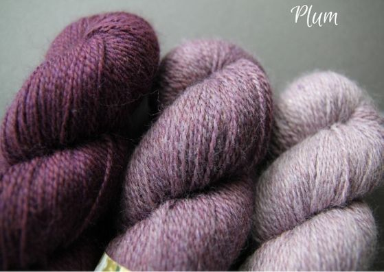 Skeins showing three shades of plum John Arbon Textiles merino 4 ply wool available getting darker from right to left.