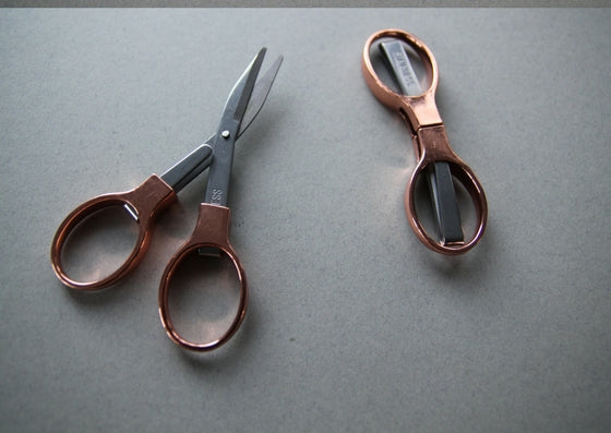 Grey background with rose gold fold away scossors shown in two positions L-R: fulley extended and blades closed, fully closed.