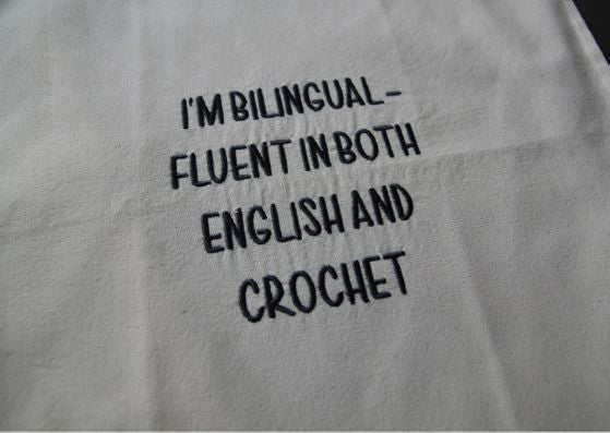 "Close up of natural cotton bag with black text saying "" I'm bilingual - fluent in both English and crochet""."