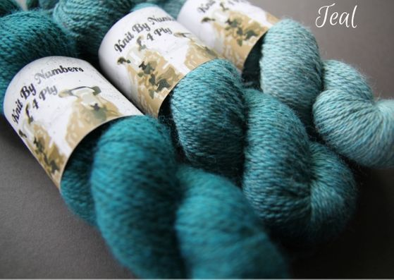 Skeins showing three shades of teal John Arbon Textiles merino 4 ply wool available getting darker from right to left.