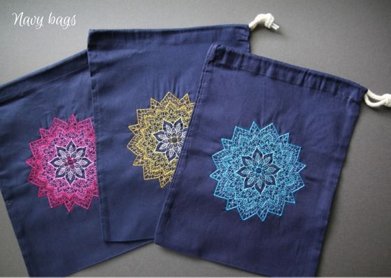 Navy mandala project bags: three navy cotton bags with a mandala on each fading from a dark outside to lighter inner.  L-R the mandalas are pink, yellow and turquoise.
