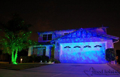 blisslight blue indoor projector shown in use outdoors during warm and dry weather for spectacular displays combined with a green spright at the tree base - Laser Lights For Christmas Outdoors