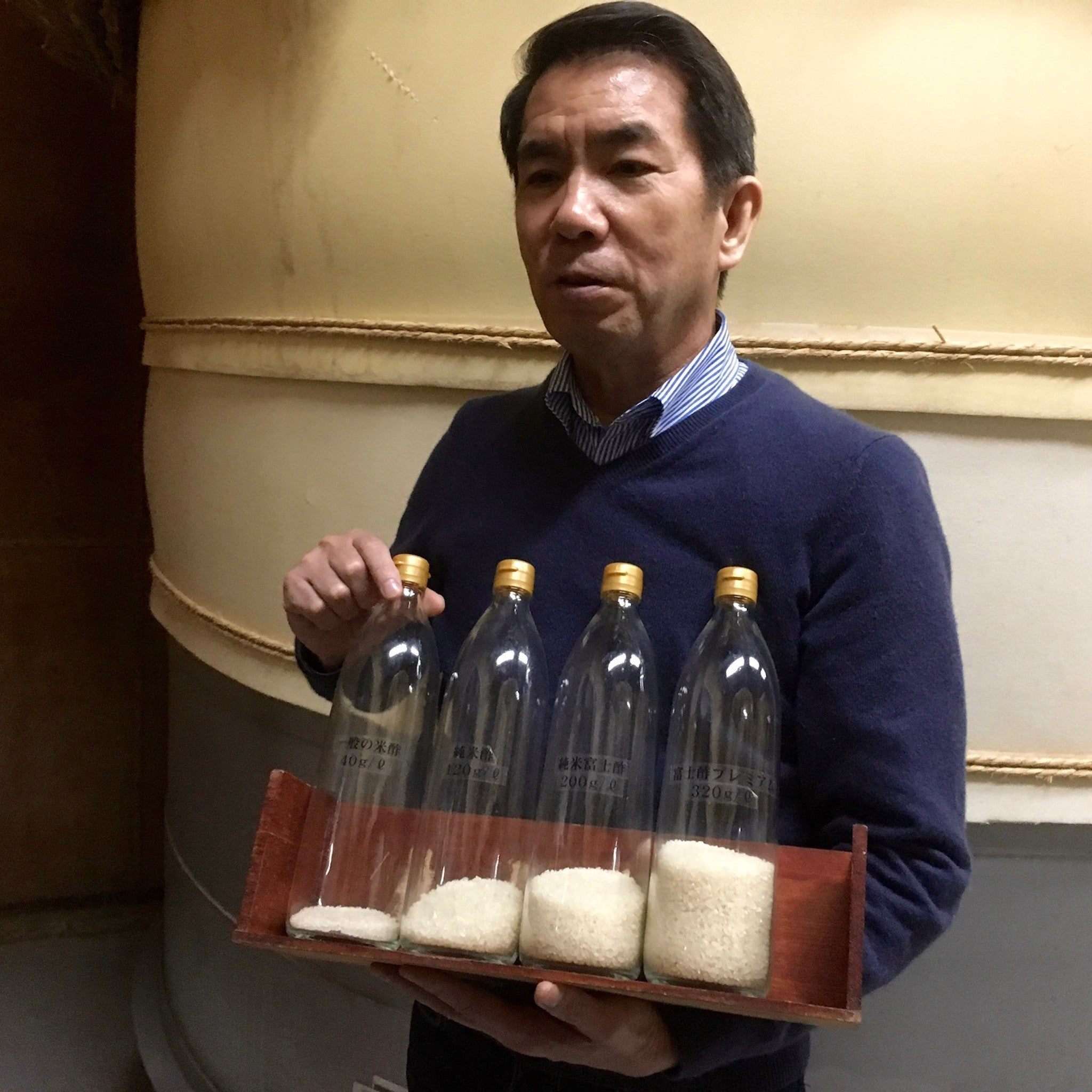 Iio-san comparing amounts of rice used to make rice vinegar