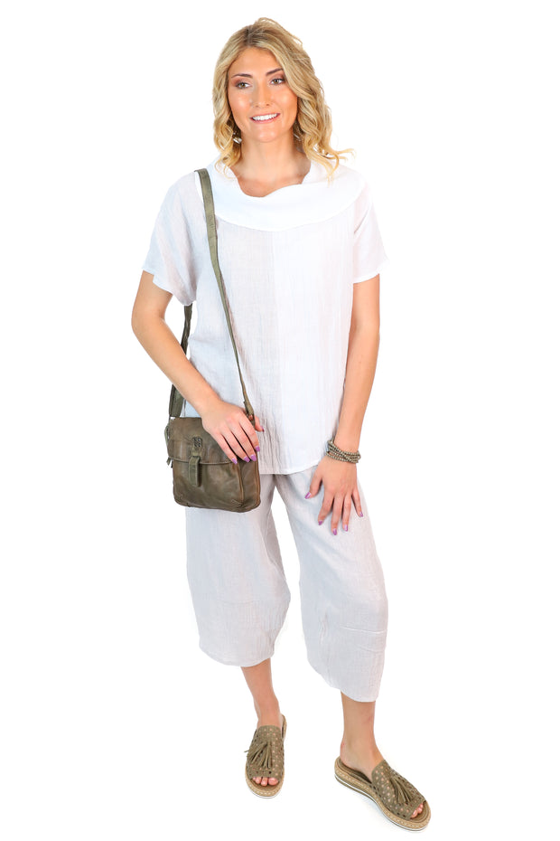 A grey and white linen outfit made by grey pants and with a white and grey cowl neck top.