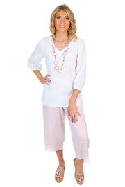 An all linen outfit made of soft pink pants and a white top.