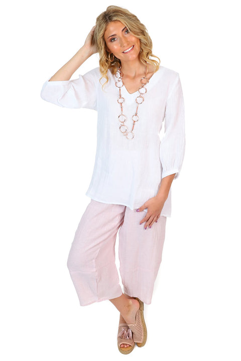 A white linen top and pink linen pants paired with pink espadrilles and a rose gold necklace.