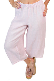 Pink linen pants with an elastic waist, pockets and ankle length crop.