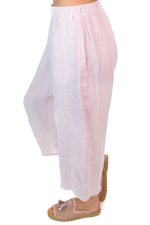 Side view of pink linen pants including pockets, wide legs and an ankle length finish.