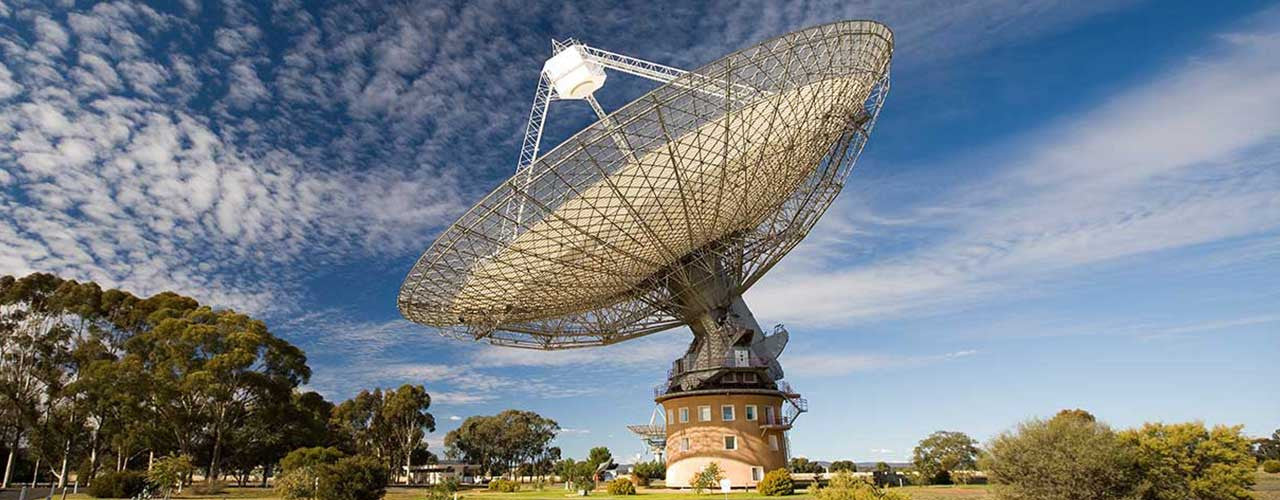Parkes Radio Telescope surrounded by grass and trees - the Dish shop - blue sky background and scattered white clouds
