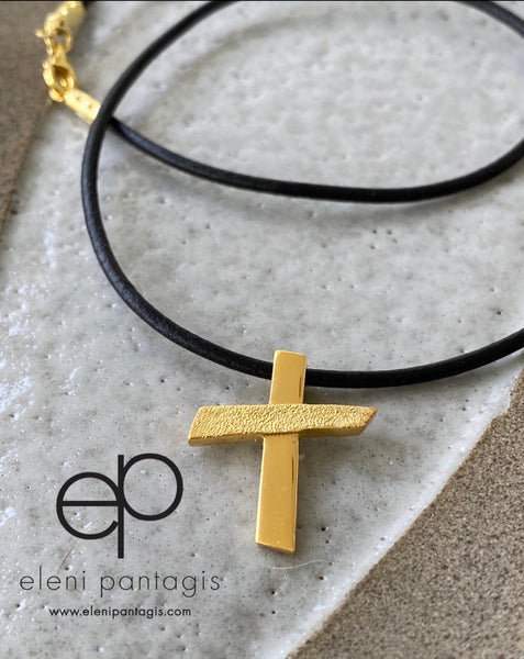 gold cross with black leather necklace