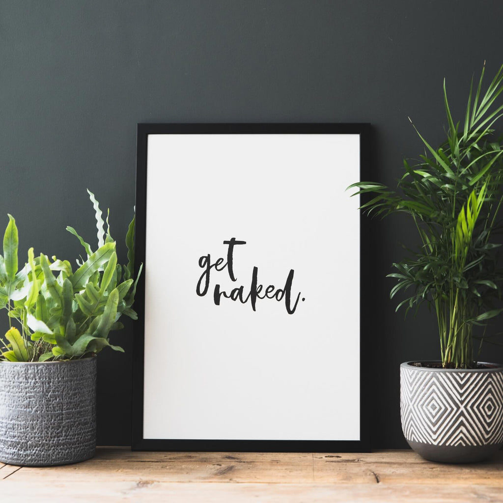 White print with black brush font in a black frame that reads 'get naked' with a house plant either side