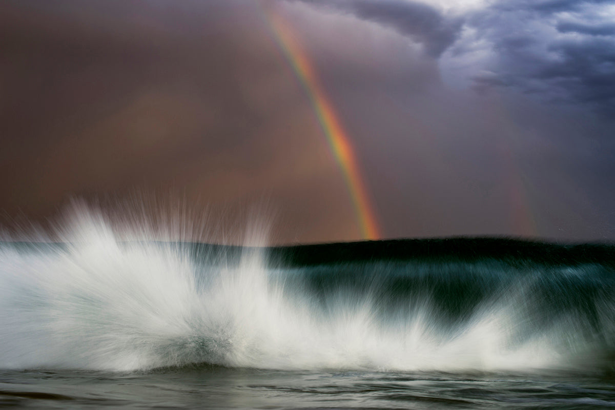 image of rainbow falling behind crashing wave by Ray Collins
