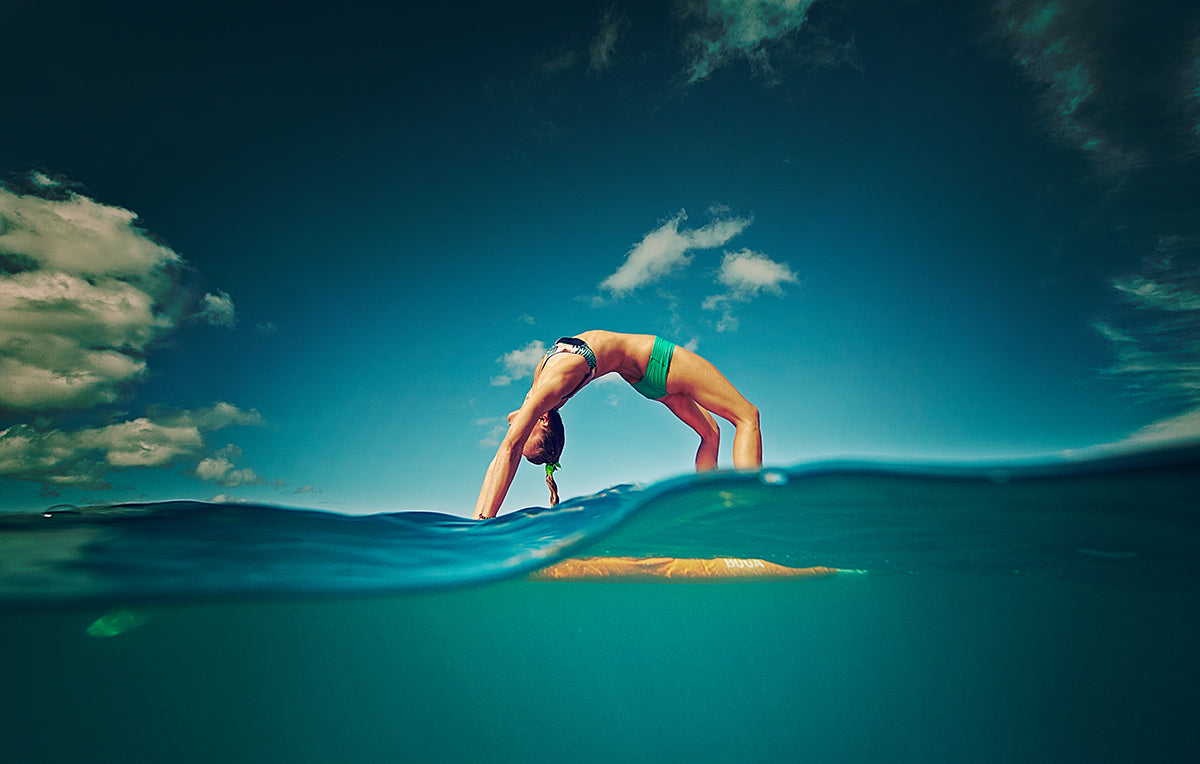 photo of a woman arching over her surfboard taken with an AquaTech camera water housing
