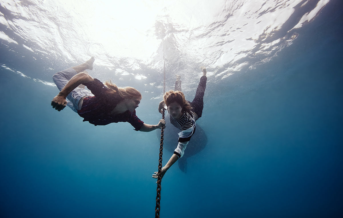 photo of two women underwater holding onto a chain