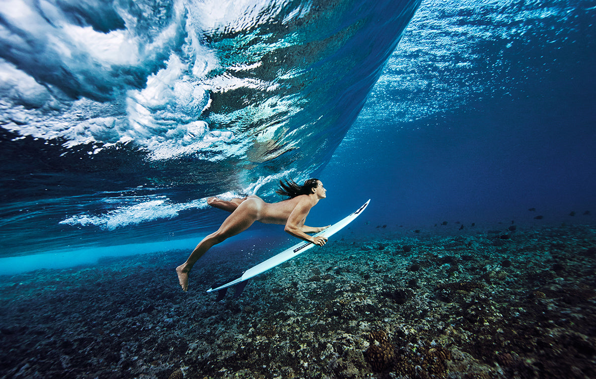 photo of a swimmer duck diving under a wave in his birthday suit