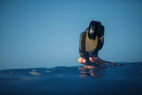 Diver holding AxisGo water housing above the ocean water