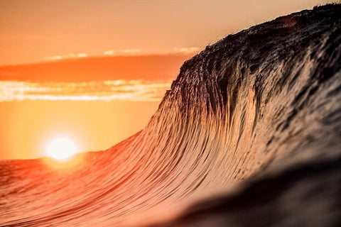Wave cresting during sunset by Lloyd Meudell