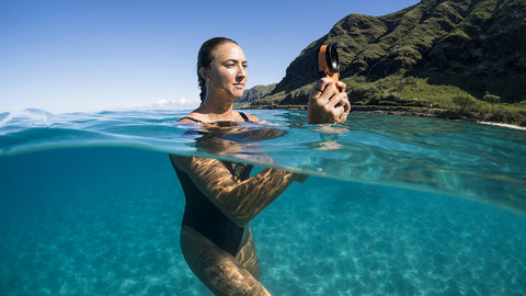 woman in ocean taking pictures with iPhone housing