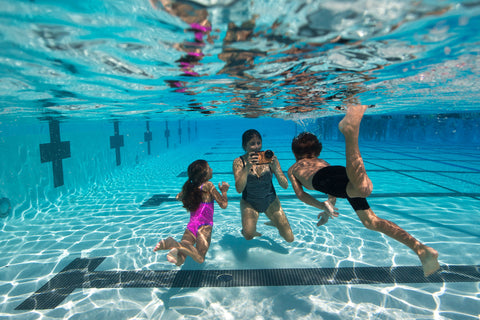 family swimming underwater in a pool using the AxisGO water housing for the iPhone 7