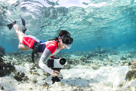 woman snorkeling in ocean with iPhone 7 water housing and pistol grip