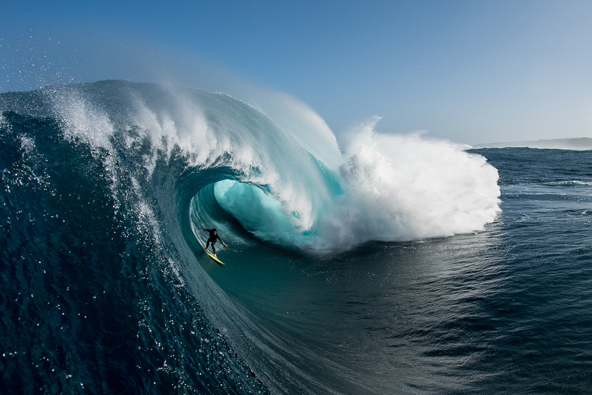 man surfing down giant crashing wave by Russell Ord