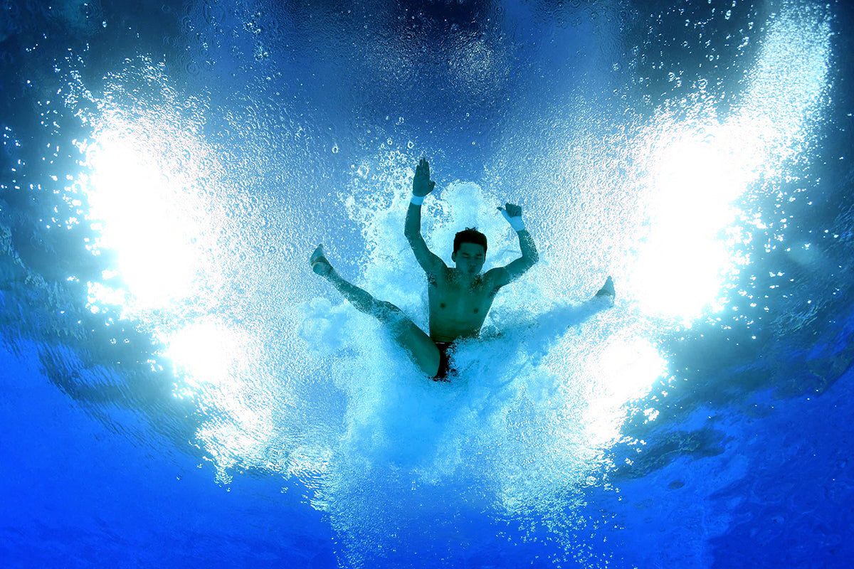 photo of man diving into water taken with water housing