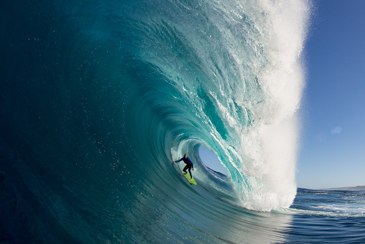 man surfing through wave barrel photo by Russell Ord