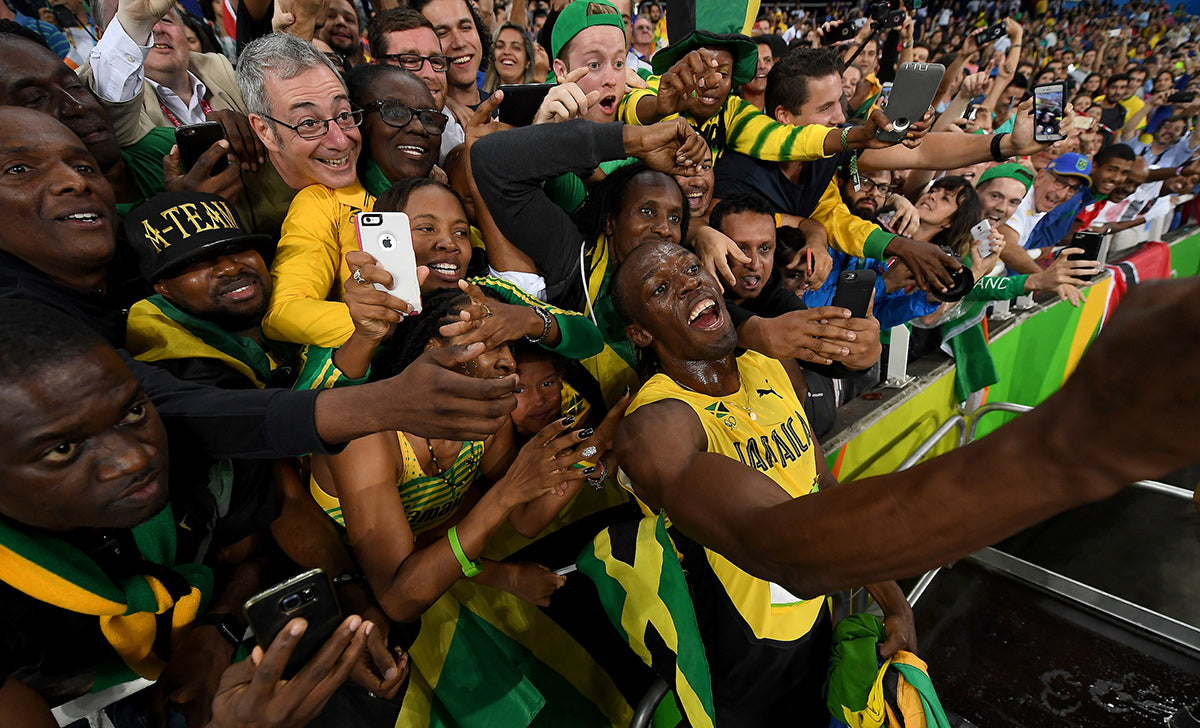 photo of Usain Bolt in front of cheering fans by Donald Miralle