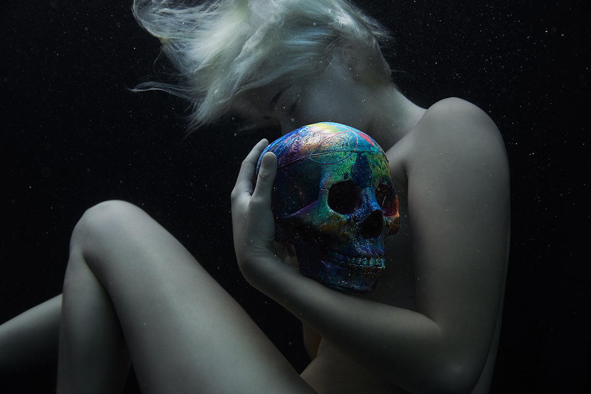 photo of a woman caressing a colorful skull underwater by Steven Lippman
