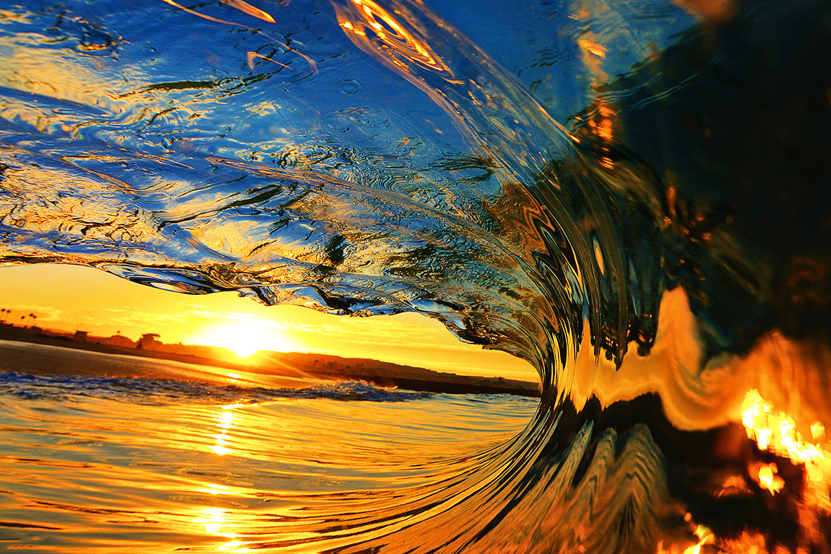 sunset reflected in ocean surface and curling wave