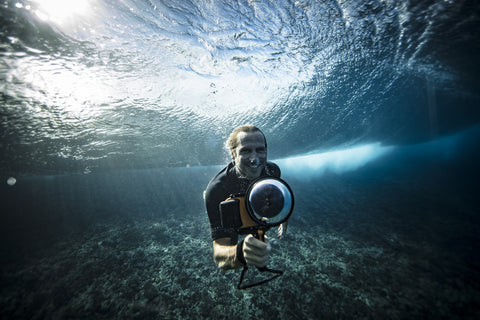 man swimming in ocean with iPhone water housing and dome lens port
