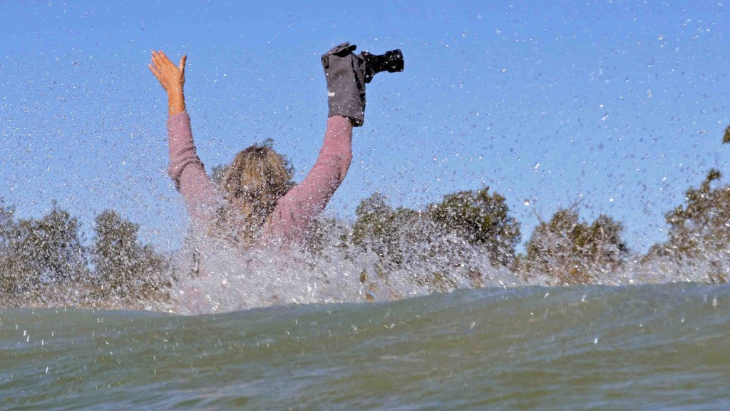 Deb Morris with underwater camera case splashing in wave