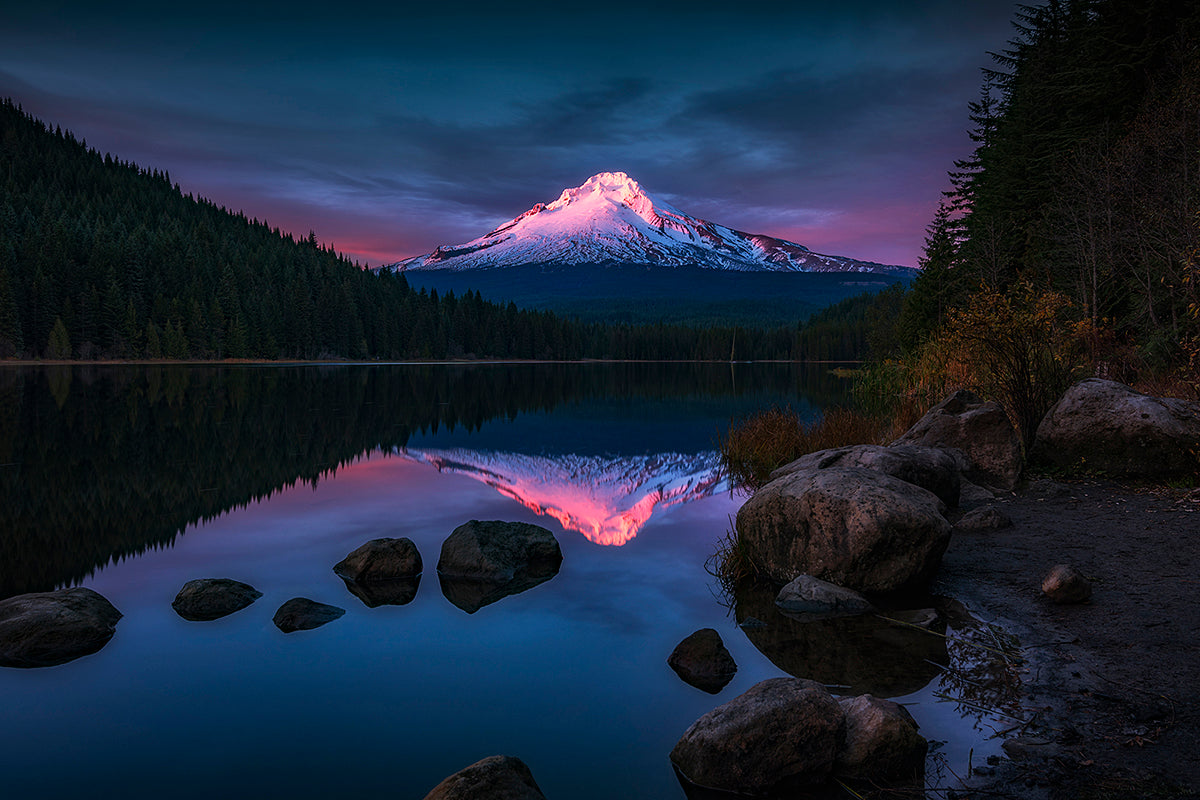 photo of a snowy mountain lit purple by the sun on the horizon