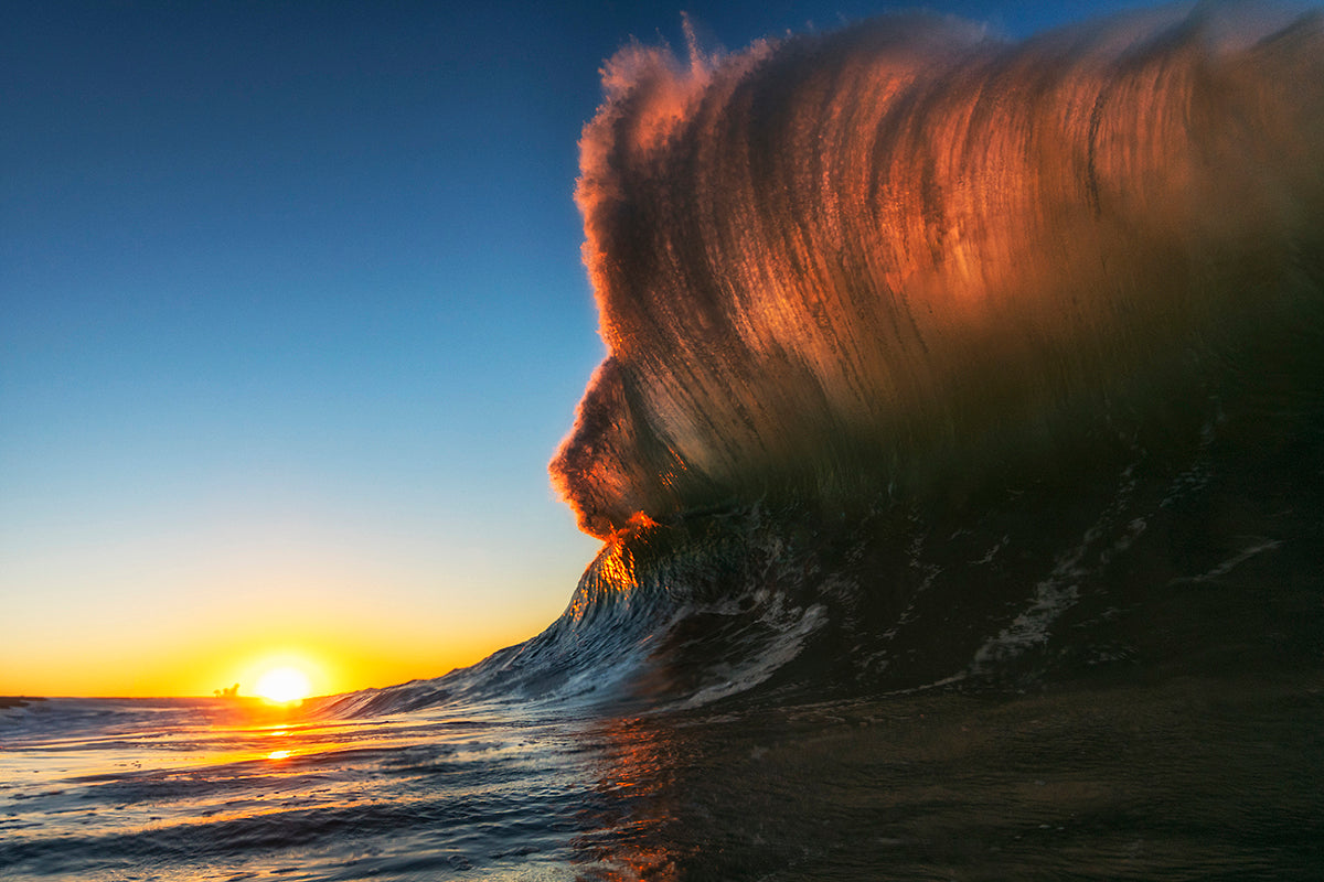 Crashing wave lit red by the sunlight