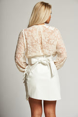 A Winter White Leatherette Wrap Mini Skirt with Ruffle Edge