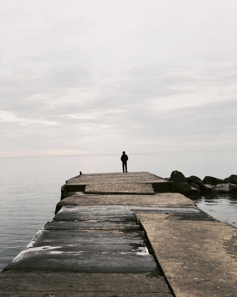 A man stands at the edge of the sea.