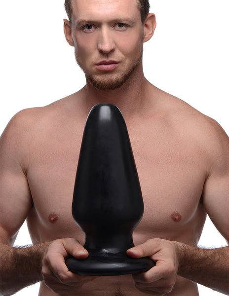 XR Brands MC Gigantor XXXL Tapered Butt Plug Held By A Satisfied Model