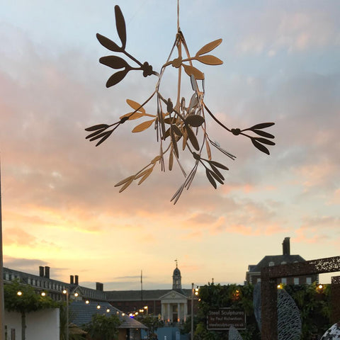 Image of mistletoe against a sunset sky, with the Chelsea Pensioner's Hospital in the background