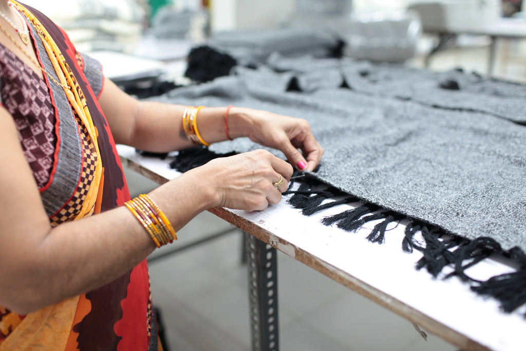 woman in sari completing knit organic blanket